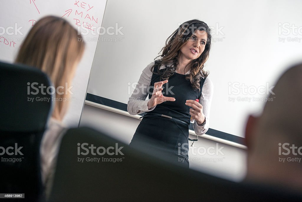 Female standing in front of people doing business training stock photo