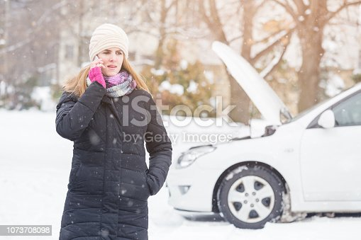 Young woman using smartphone to call road assistance. Winter and vehicle concept.