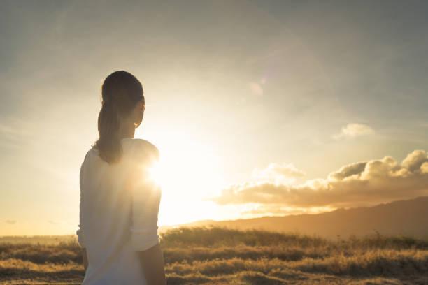 kobieta stojąca na górze patrząc w kierunku pięknego zachodu słońca. - nadzieja zdjęcia i obrazy z banku zdjęć
