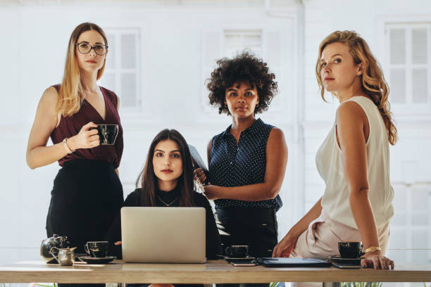 Female startup business team Group of multiracial businesswomen in casuals together at office desk and looking at camera. Female startup business team portrait. four people stock pictures, royalty-free photos & images