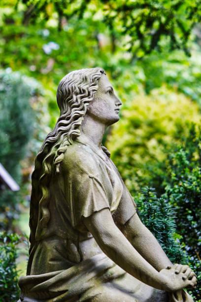 weibliche statue auf einem friedhof - waldfriedhof stock-fotos und bilder