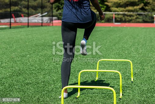 976685710 istock photo Female stepping over yellow hurdles 975221678