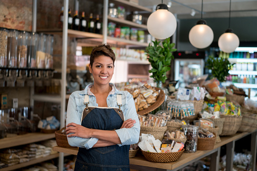 Latin American woman working at a grocery store - small business concepts