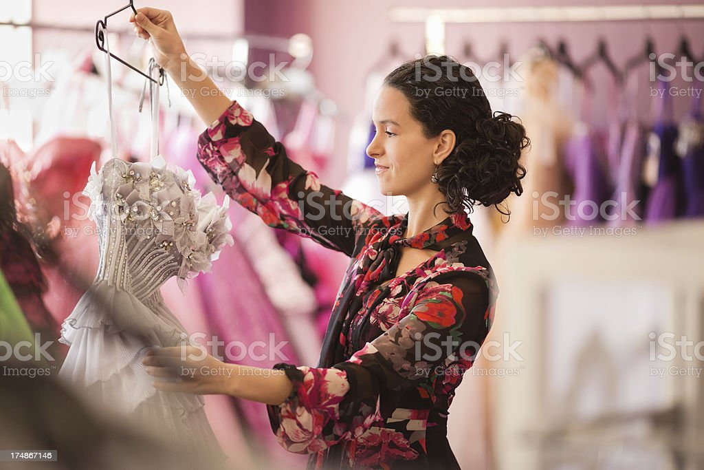 Female Store Owner Examining Evening Gown royalty-free stock photo