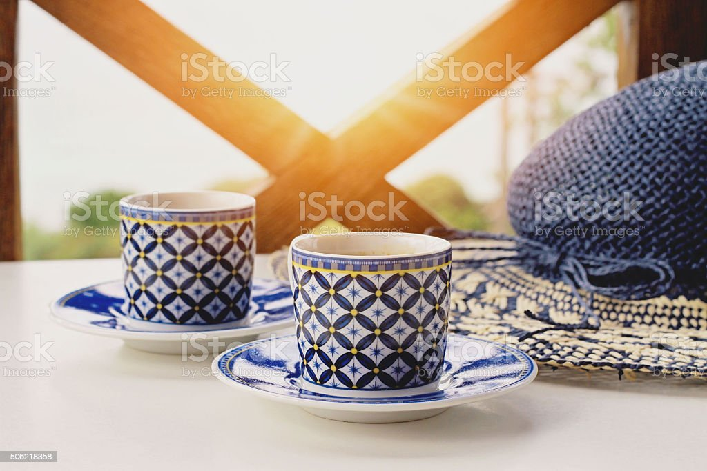 Female straw hat and two cups of coffee stock photo