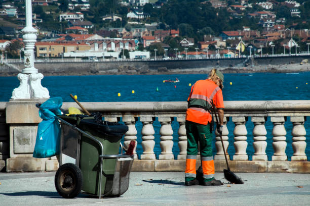 Female street sweeper with cart, broom and dustpan in San Lorenzo beach in Gijón, Spain.. Gijon, Spain-August 31, 2018: Rear view of female street sweeper with cart, garbage can, broom and dustpan working on the sidewalk, waterfront by the beach, sea in the background, summer day in San Lorenzo beach in Gijón, Asturias, Spain.. street sweeper stock pictures, royalty-free photos & images