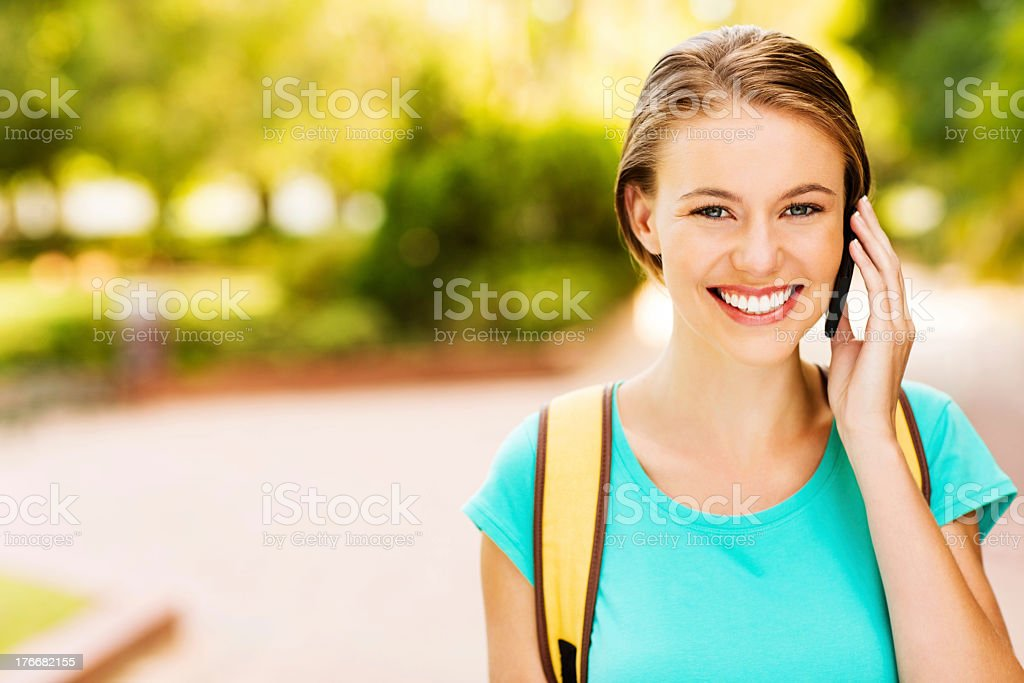 Female Student Answering Call On Smart Phone At Campus royalty-free stock photo