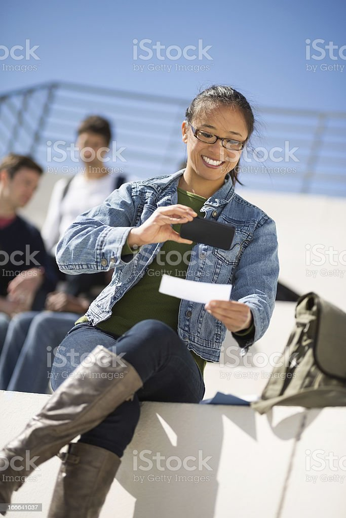 Female Student Depositing Check Through Phone stock photo
