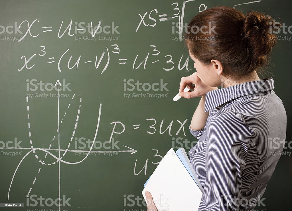 Female student figuring complex math problem at chalkboard stock photo