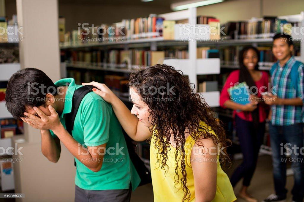 Female student helping sad friend stock photo