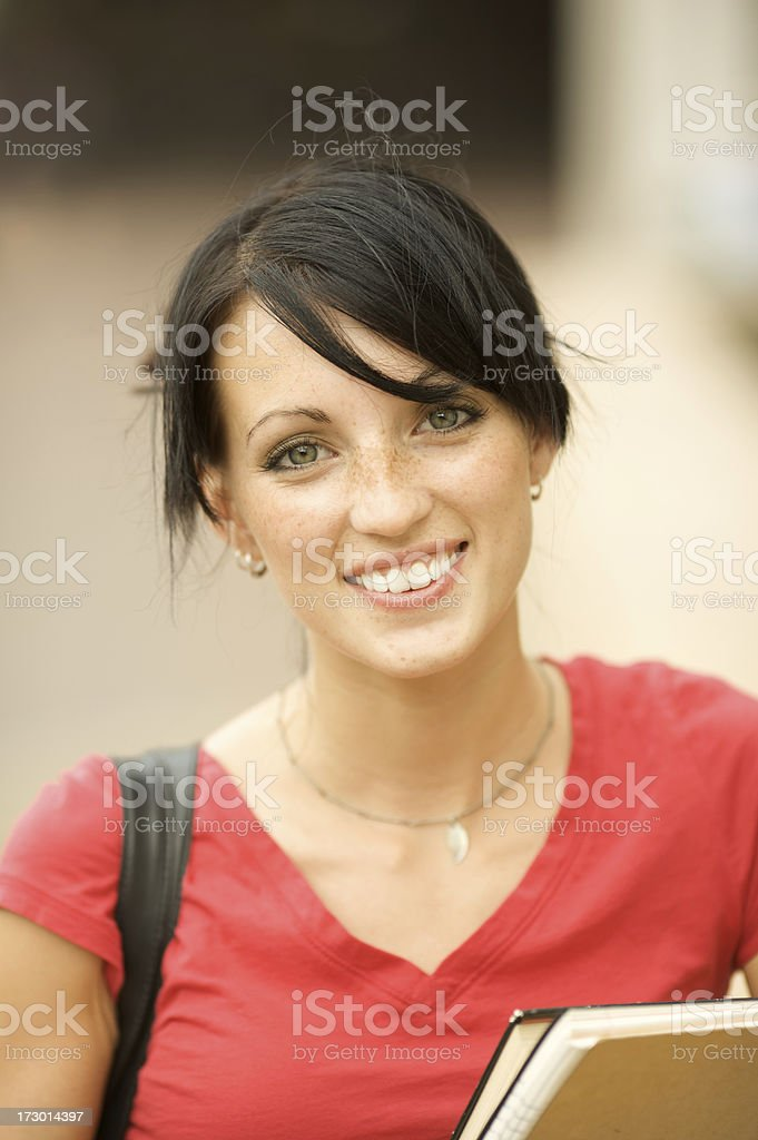 Female student holding books outdoors royalty-free stock photo