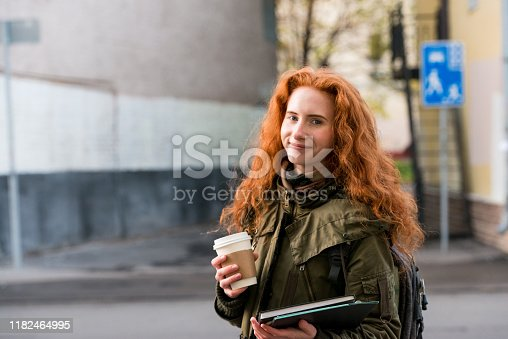 The young female student holds a cup of coffee and school books while posing for a photo.