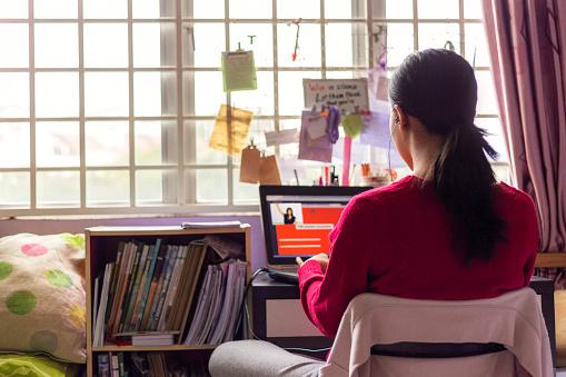 Asian Teenage girl wearing earphones sitting in front of lapttop, attending online video classroom with teacher in her bedroom