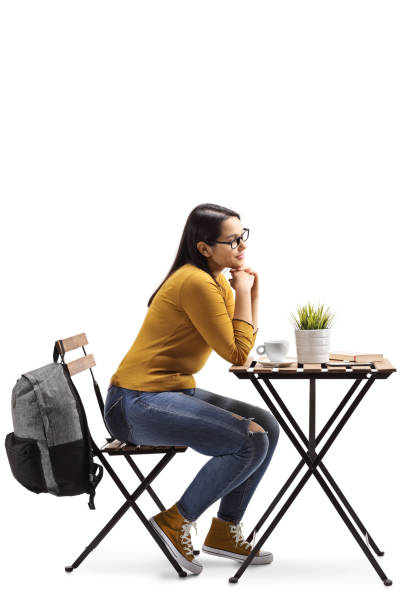 Female student in a cafe sitting at a table with coffee stock photo