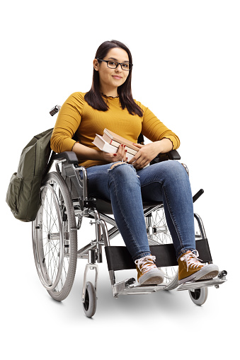 Full length shot of a female student in a wheelchair holding books isolated on white background