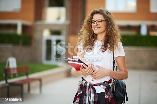 Female student in campus with books in her arms and bag on shoulder.
