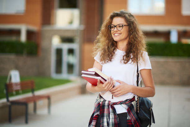 Female student in campus. Female student in campus with books in her arms and bag on shoulder. public building stock pictures, royalty-free photos & images
