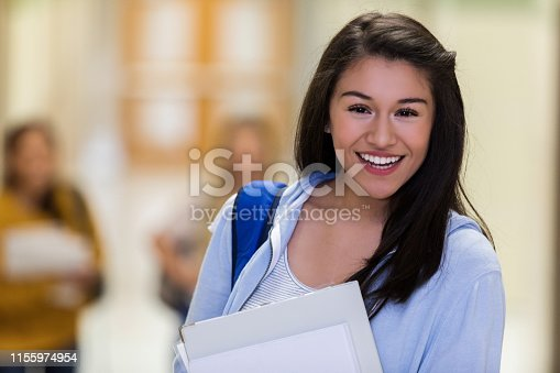 istock Female student in corridor gives class photographer smile 1155974954