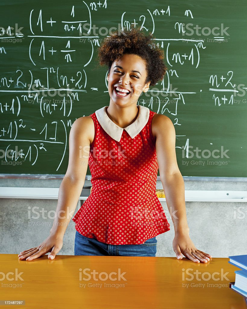 Female student in front of blackboard Happy female student standing in front of blackboard and smiling at the camera. 18-19 Years Stock Photo