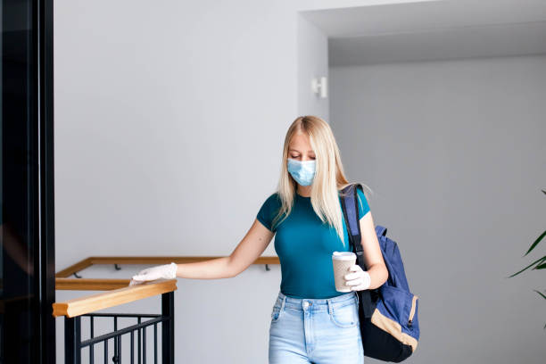Female student in mask indoors going to exams in high school. Sad young woman in empty university. stock photo