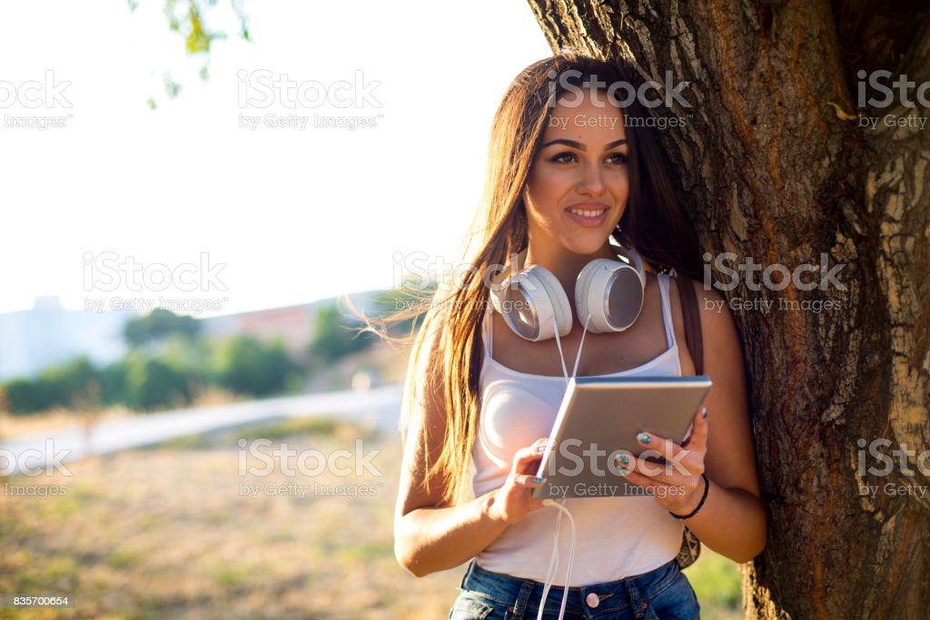 Female student in the park using portable information device.
