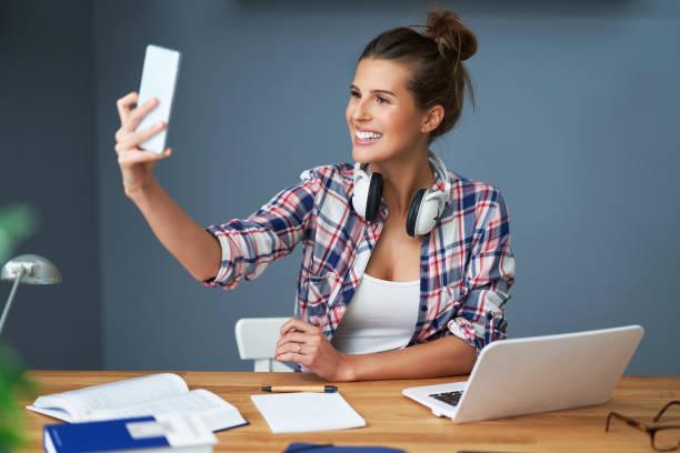 Studentin lernt zu Hause und macht Selfie – Foto
