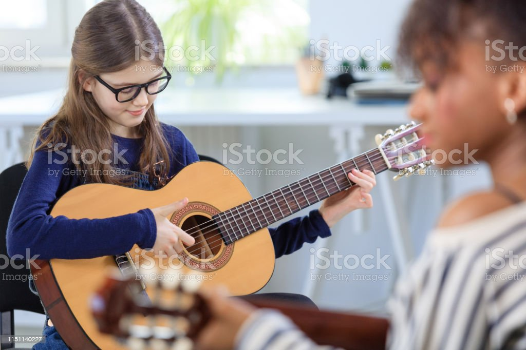Female student learning guitar from trainer Pre-adolescent girl playing guitar. Student is learning music from female guitarist. They are in training class at conservatory. 10-11 Years Stock Photo