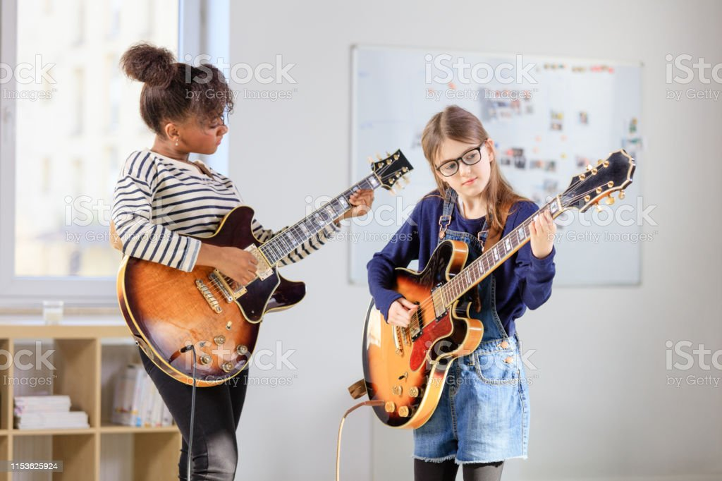 Female student learning guitar from trainer Girl playing electric guitar. Student is learning music from female guitarist. They are in training class at conservatory. 30-34 Years Stock Photo