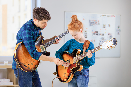 Female Student Learning Guitar From Trainer Stock Photo - Download Image Now