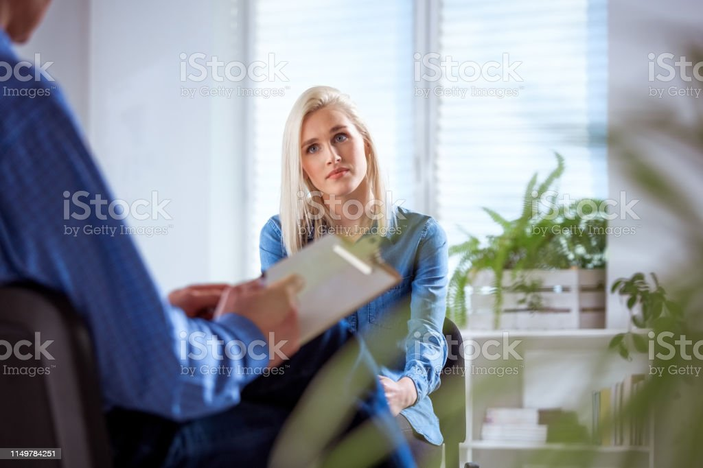 Female student listening to therapist in meeting Young woman listening to therapist during session. Female student is discussing with mental health professional. They are in university. 18-19 Years Stock Photo