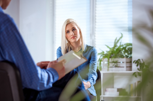 Female Student Listening To Therapist In Meeting Stock Photo - Download Image Now