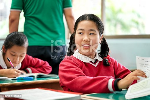 Schoolgirl looking away while reading book at desk. Female student is learning in high school. She is sitting against teacher in classroom.