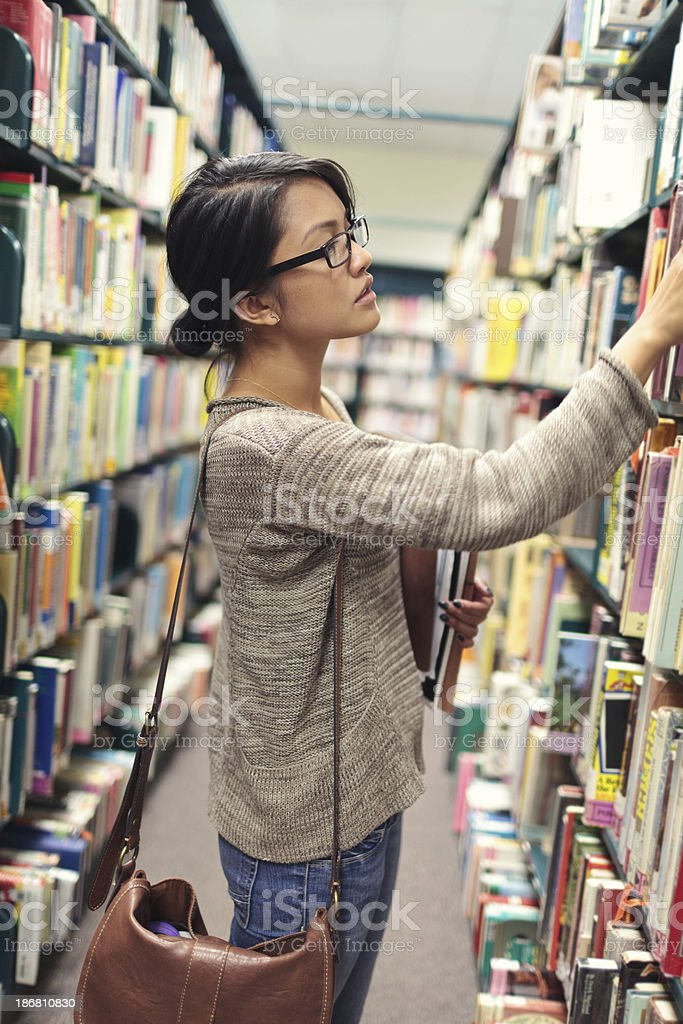 Female student looking for a book at the library royalty-free stock photo