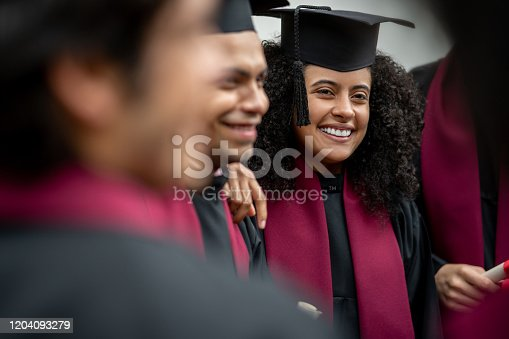 Happy female student with a group of friends on her graduation day  - education concepts