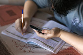 istock Female student making homework tasks while using smartphone, selective focus 899040334