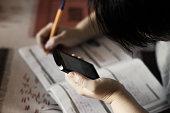 istock Female student making homework tasks while using smartphone, selective focus 899040342