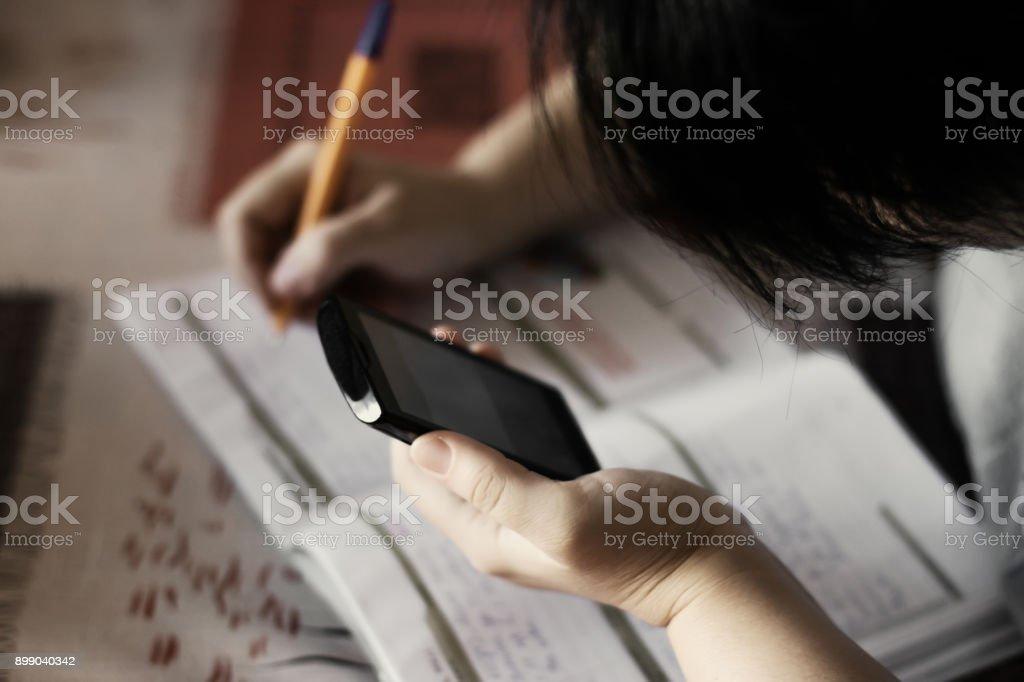 Studentin macht Hausaufgaben während mit Smartphone, selektiven Fokus – Foto