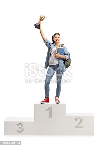 istock Female student on a winner's pedestal holding a gold trophy 1030345134