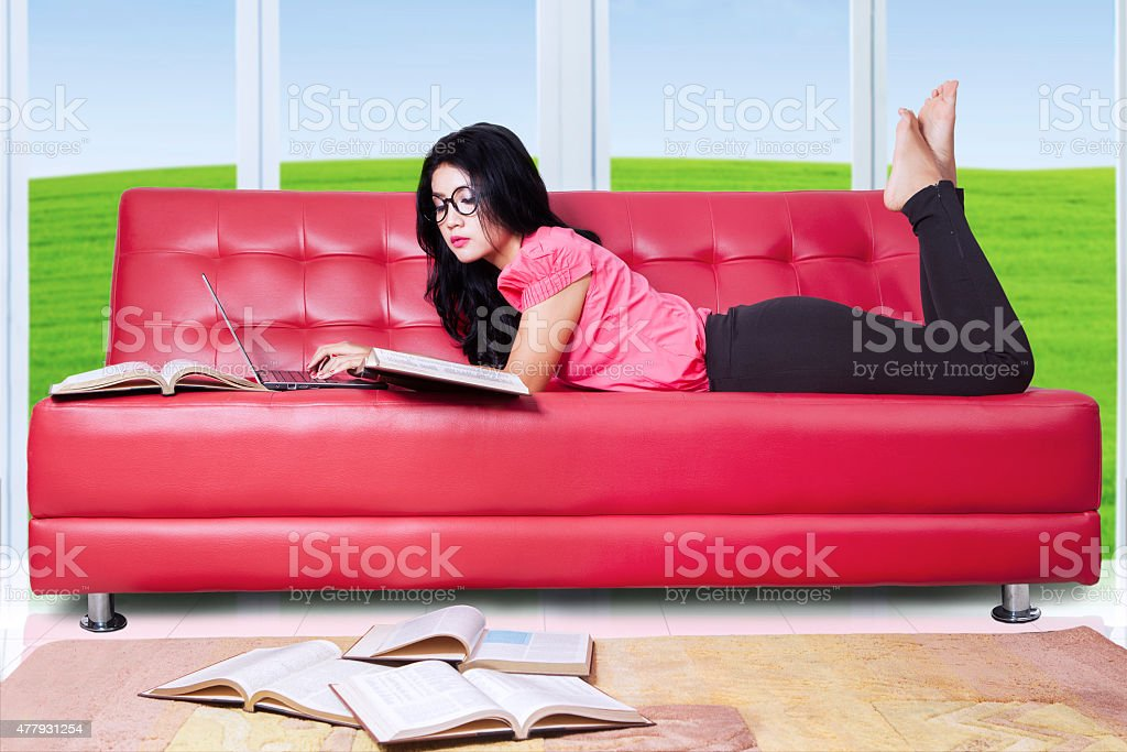 Marvelous Female Student On Sofa With Laptop And Books Stock Photo Machost Co Dining Chair Design Ideas Machostcouk