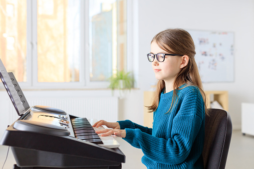 Female Student Playing Piano In Music Class Stock Photo - Download Image Now