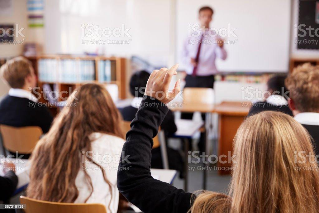 Aluna, levantando a mão para perguntar em sala de aula foto de stock royalty-free