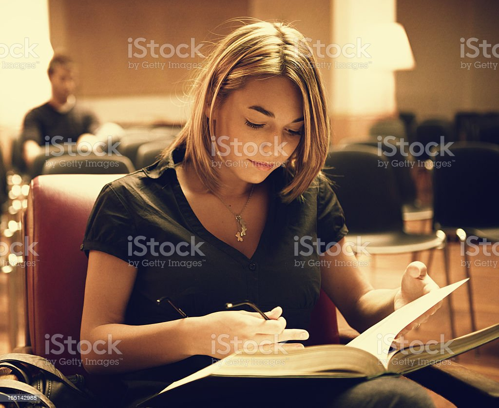 Female Student reading a book in an empty library royalty-free stock photo