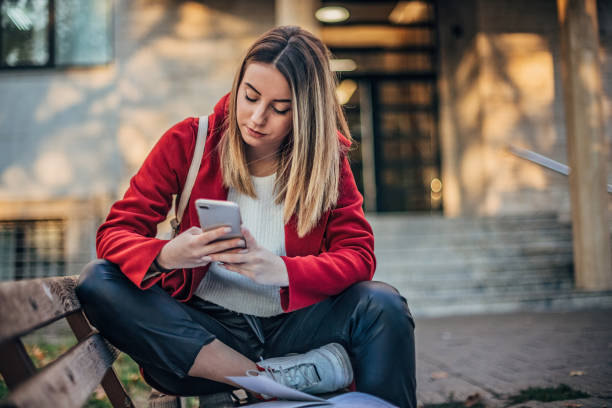 Female student reading book and learning fo exam on the bench stock photo