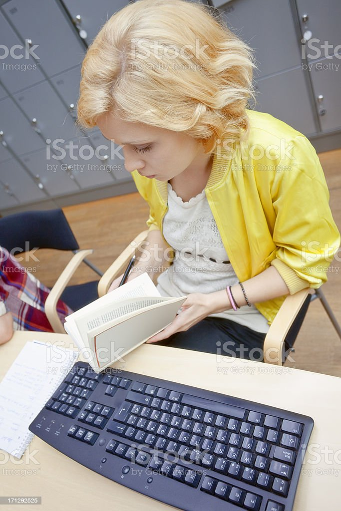Female Student Reading Book at Library, Computer Keyboard in Foreground royalty-free stock photo