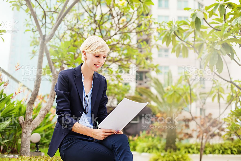 female student reading documents stock photo
