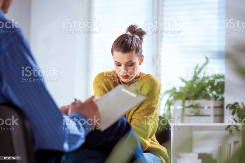Female student sharing problems with therapist Woman with low self esteem sharing her problems during therapy session. Female student is discussing with mature social worker. They are in meeting at lecture hall. 18-19 Years Stock Photo