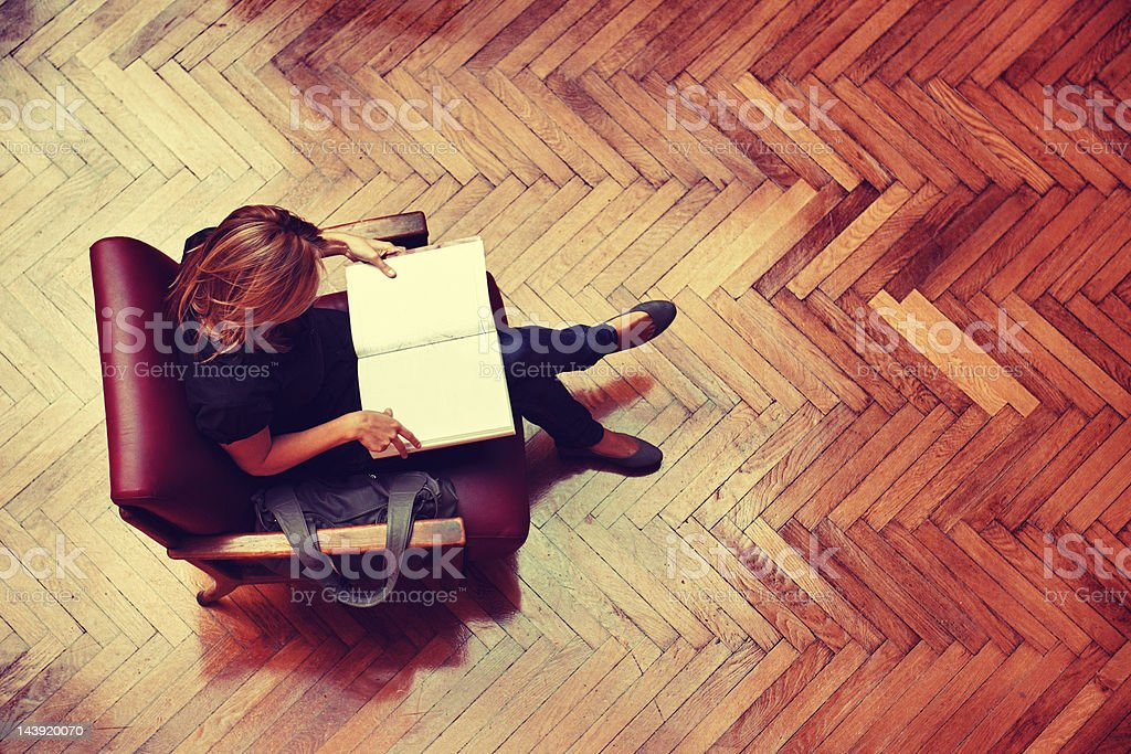 Female student sitting and reading a book royalty-free stock photo