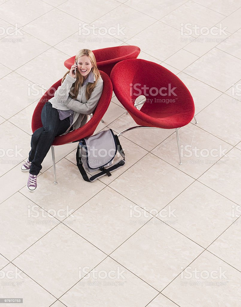 Female student sitting in chair talking on cell phone royalty-free stock photo