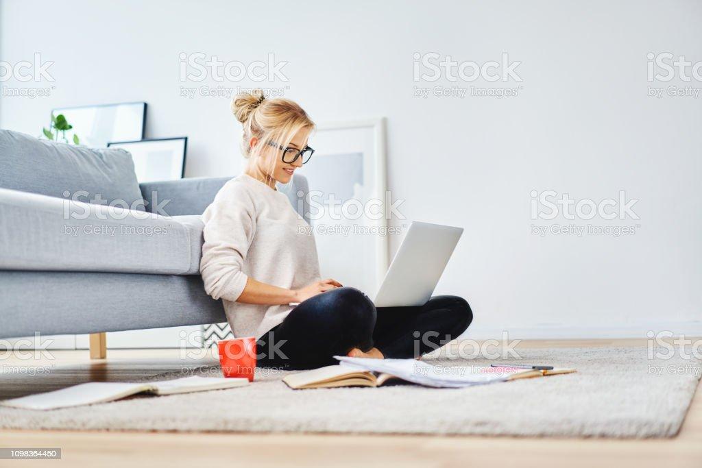 女學生坐在她的公寓地板上, 筆記本電腦和筆記學習 - 免版稅20多歲圖庫照片
