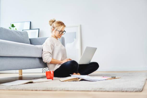 estudante sentada no chão do apartamento com laptop e notas de estudo - laptop - fotografias e filmes do acervo